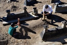 A man and a child pray beside the grave of one of their relatives during the ceremony. JP/Stefanus Ajie