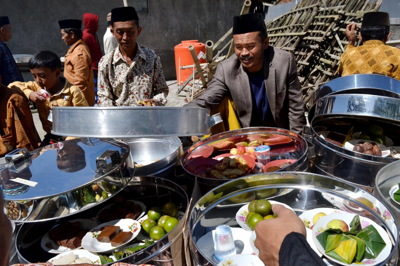 Some villagers share food kept inside tenong (containers made of aluminum or bamboo), which they brought from home during the ceremony. JP/Stefanus Ajie