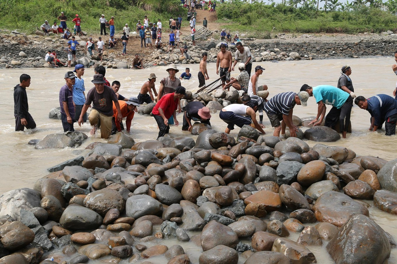Hard work: Villagers collect rocks from the river to build pillars for the emergency semi-permanent bridge. JP/ PJ Leo