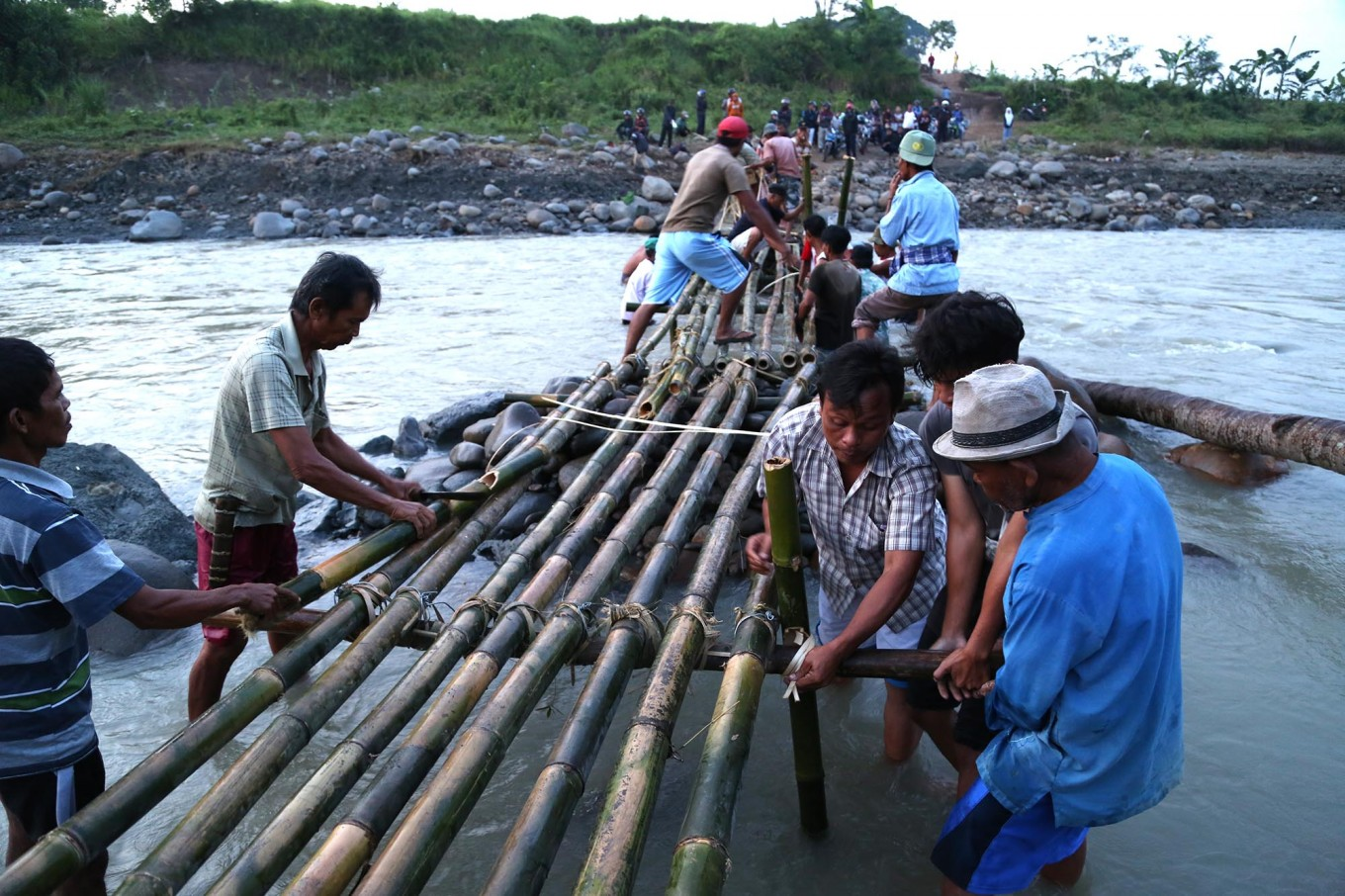 Coming together: Villagers from both sides of the river try best to build an emergency semi-permanent bridge using bamboo. JP/ PJ Leo