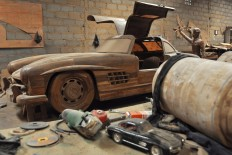 A teakwood replica of a Mercedes-Benz 300 SL gull-wing is in the background while the model of the car is in the foreground. JP/Magnus Hendratmo