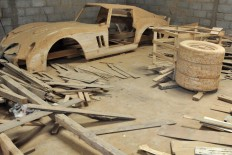 The body of a car and three tires are seen in the corner of the workshop. All of the car parts are made of teakwood waste. JP/Magnus Hendratmo