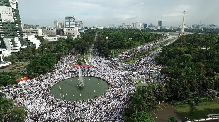 This aerial view shows Indonesian Muslims gathering at Jakarta's National Monument Park as part of a rally against Jakarta's Christian Governor Basuki Tjahaja Purnama, better known by his nickname Ahok, on December 2, 2016. More than 100,000 Indonesian Muslims protested on December 2 against Jakarta's Christian governor, the second major demonstration in a matter of weeks as conservative groups push for his arrest on accusations of insulting Islam.