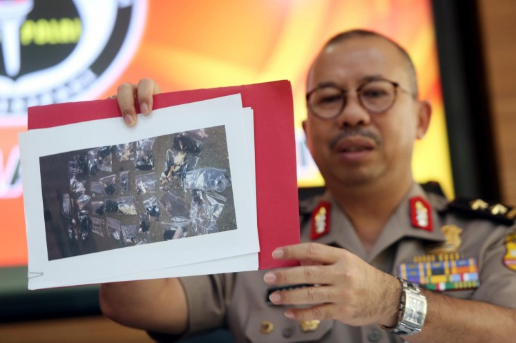 National Police spokesman Insp. Gen. Setyo Wasisto holds up a photograph during a press conference in Jakarta on May 25.