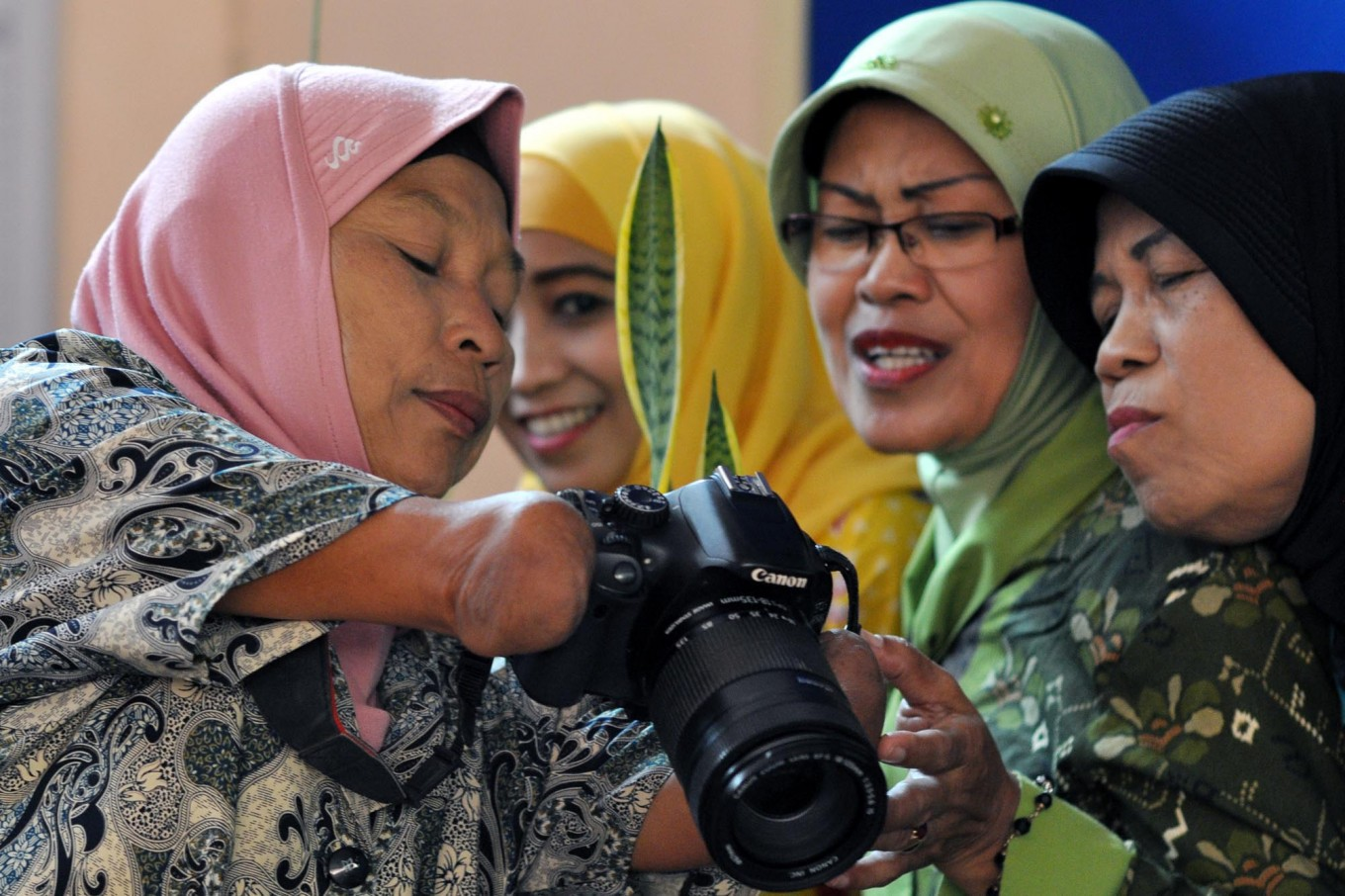 Rusidah shows pictures to her clients that can be printed postcard size and sell for Rp 20,000 each. JP/Magnus Hendratmo