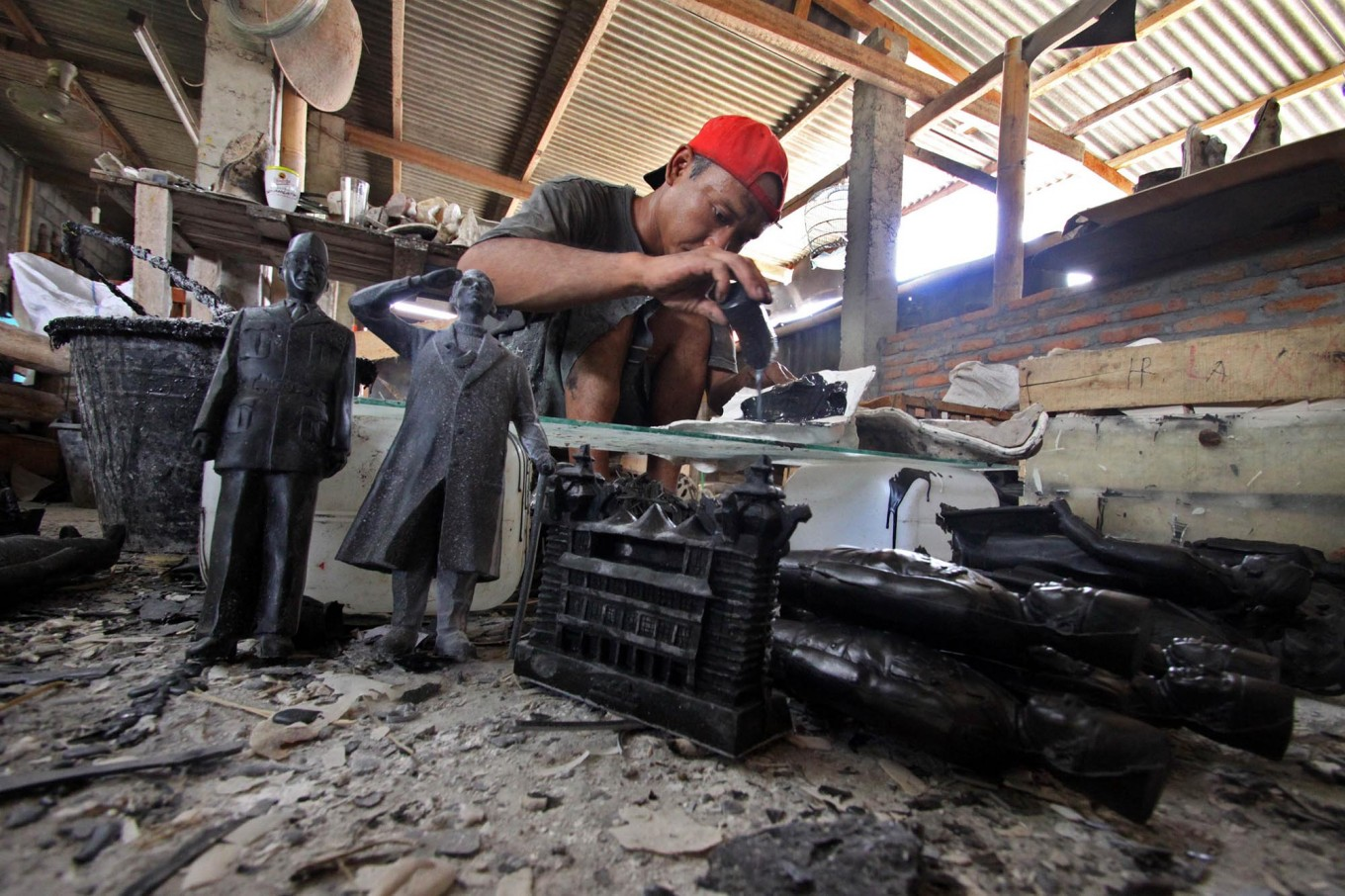 A man pours a resin liquid into a rubber sculpture mold in the Prambanan district, Yogyakarta, on Feb. 21. JP/Aditya Sagita