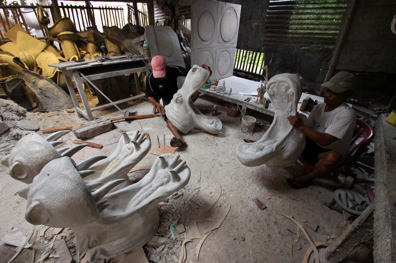 A man uses sandpaper to smooth a cement sculpture after molding it in Patuk village, Gunungkidul, Yogyakarta, on Feb. 21. JP/Aditya Sagita