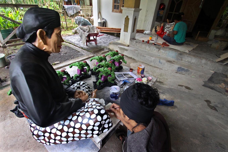A man paints batik fabric details on a Yogyakarta royal servant sculpture at Patuk, Gunungkidul, Yogyakarta, on Feb. 21. JP/Aditya Sagita