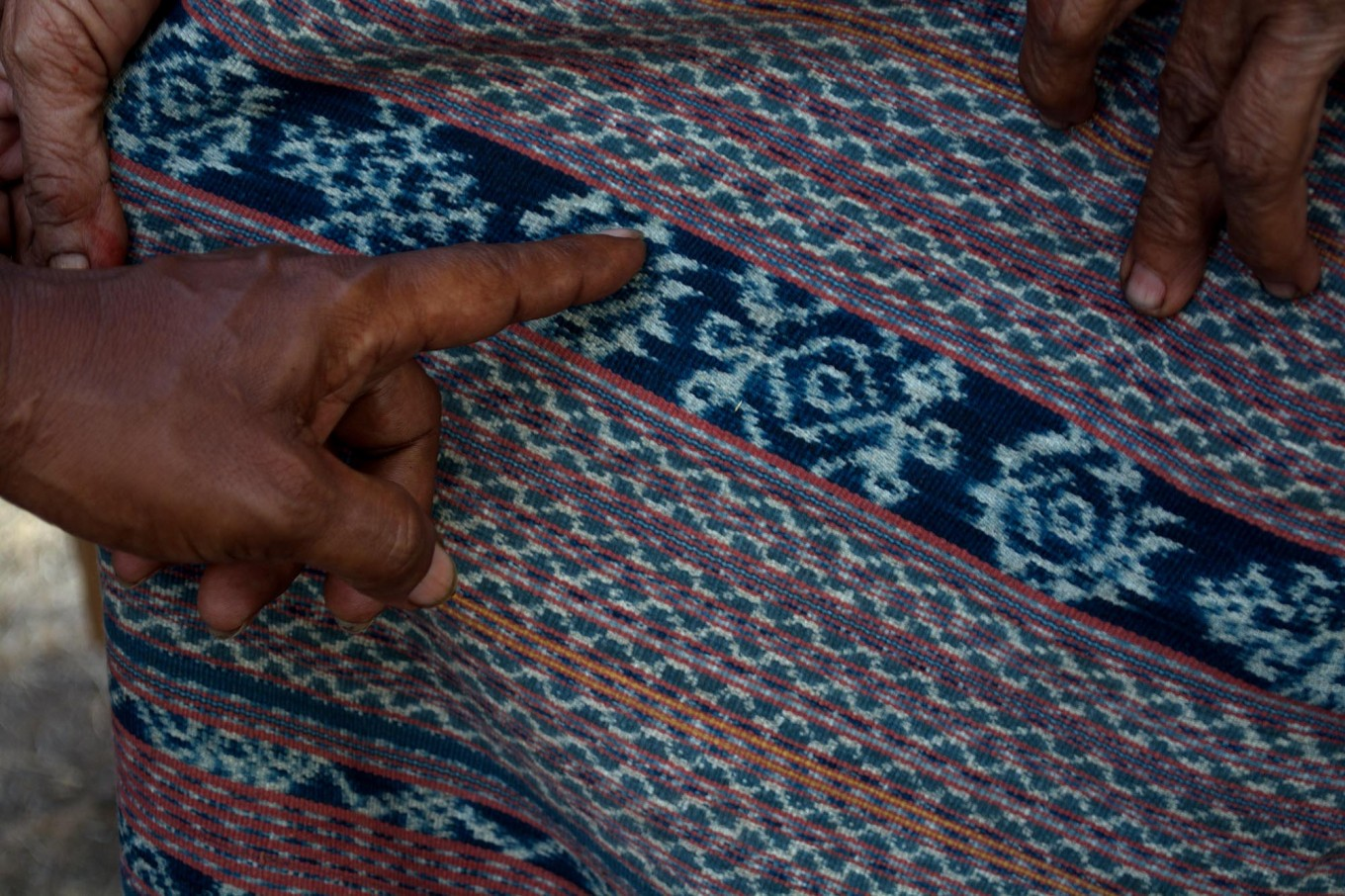 A Sikka woman points to one of the sacred symbols in the traditional ikat cloths. The motif represents women's fertility. JP/Intan Tanjung
