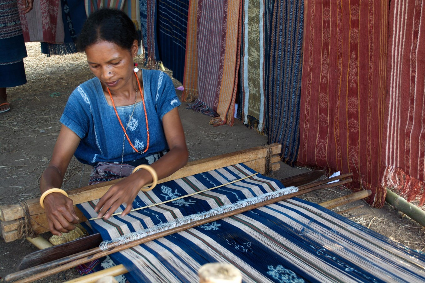Sikka women can weave beautiful ikat cloth, enhancing them with colorful motifs even without a manual. This blue-white strip featuring a gecko motif in the making is the most popular motif of Sikka's ikat cloths. JP/Intan Tanjung