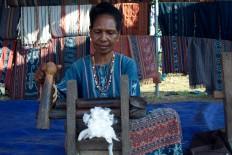 Processing cotton using a simple manual wooden machine. JP/Intan Tanjung