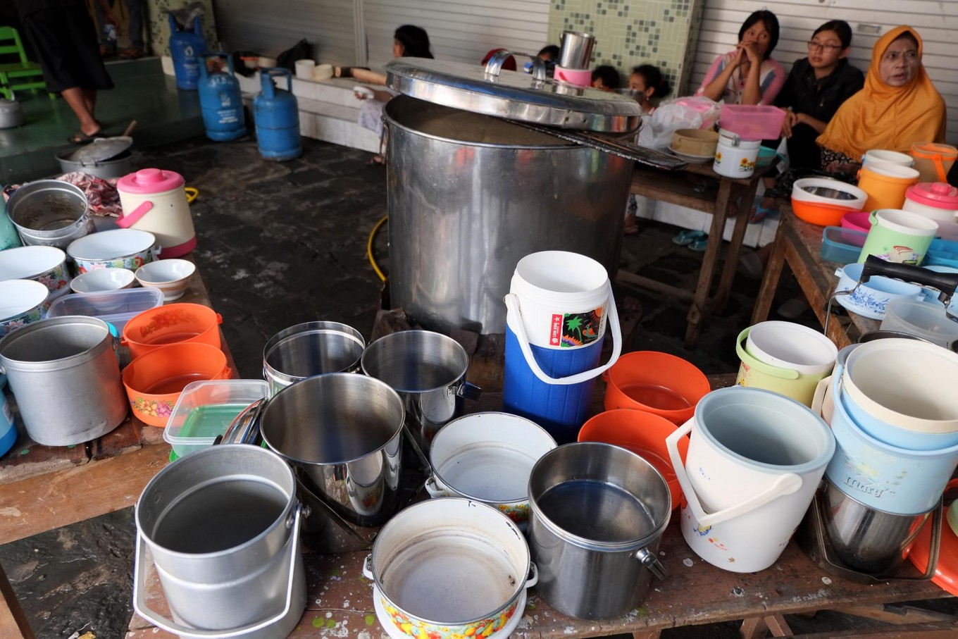 Securing a place: Residents arrive at the mosque and put their food containers on the table while patiently waiting for the porridge to be distributed. JP/ Ganug Nugroho Adi