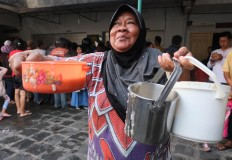 Happy go lucky: A woman smiles after securing three portions of porridge. JP/ Ganug Nugroho Adi