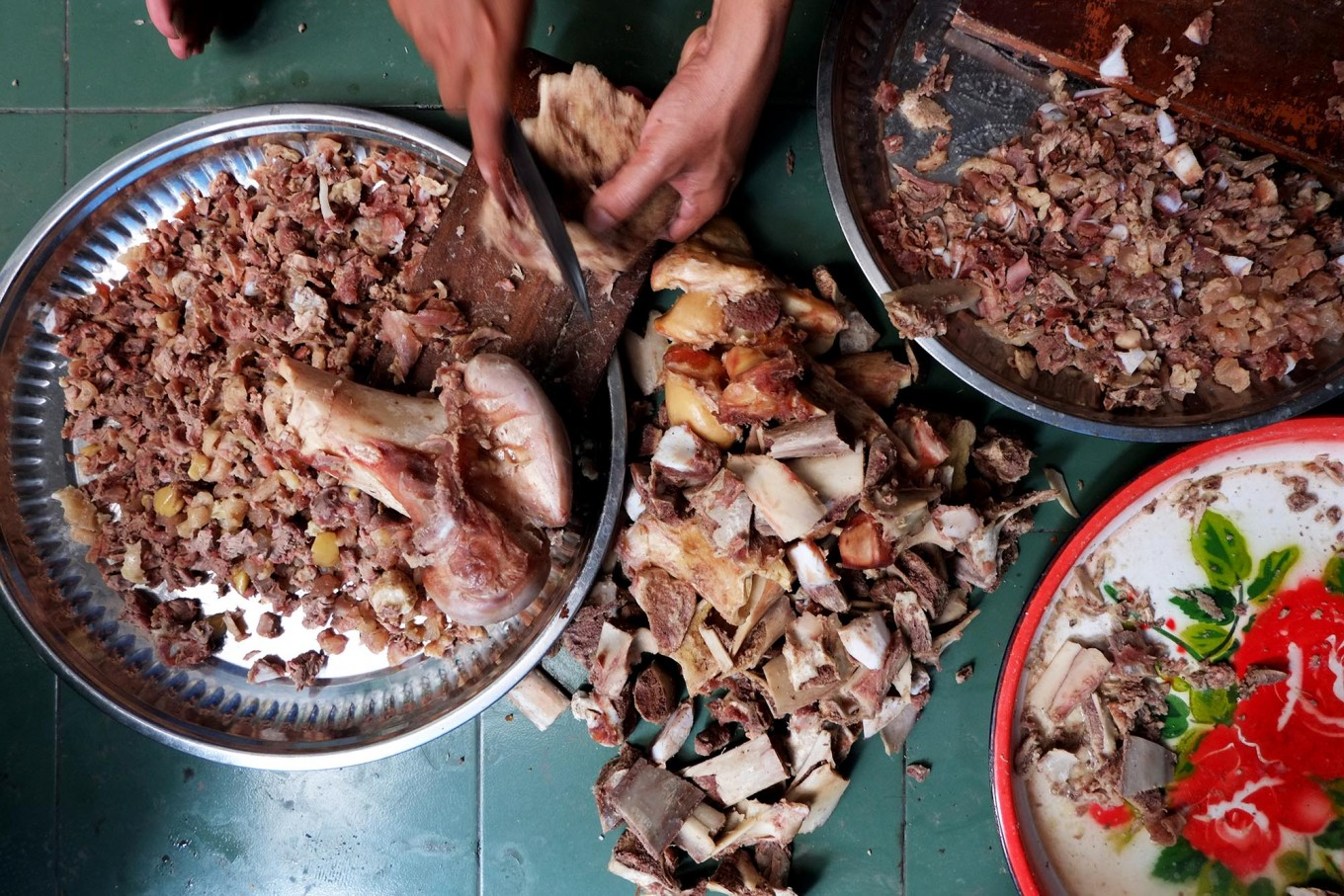 The more, the merrier: A committee member of the Darussalam Mosque in Surakarta, Central Java, slices beef into small pieces to use as one of the ingredients of Samin porridge. JP/ Ganug Nugroho Adi