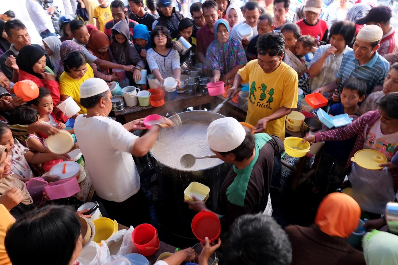 First-come, first-served: Mosque committee members distribute the porridge to hundreds of residents who come from nearby neighborhoods and outside the kampung. JP/ Ganug Nugroho Adi