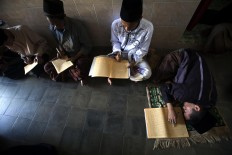 A student sleeps while others recite the Quran. Lessons start after subuh (dawn) prayers until dhuhur (midday) prayers. JP/Sigit Pamungkas