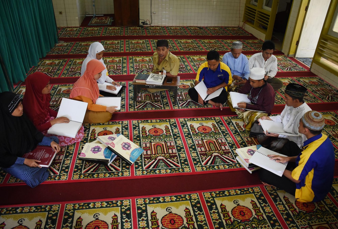 Yani (center) teaches blind worshipers to read the Quran in braille at An Nur Mosque in the Rehabilitation Center for the Blind in Janti, Malang, East Java. JP/Aman Rochman