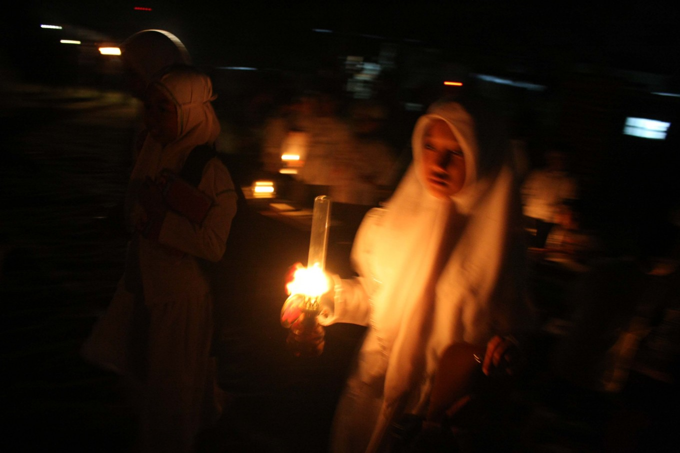 A female santri (student) carries an oil lamp to join in the tadarus (mass Quran recital) at Mojosongo, Surakarta, Central Java, on June 11. JP/Maksum Nur Fauzan