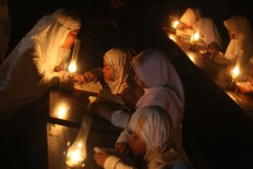 Students at the Baitul Mustofa Islamic boarding school are accompanied by an ustadzah (female Muslim teacher) to recite the Quran outdoors with oil lamps as their lighting at Mojosongo, Surakarta, Central Java, on June 11. The event is an annual activity to commemorate Nuzulul Quran (the night when the Quran was sent down to Prophet Muhammad). JP/Maksum Nur Fauzan
