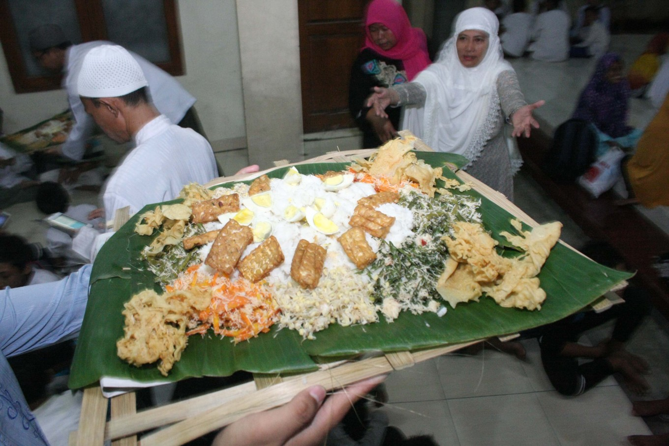 An ustadz carries a bamboo plate of rice and side dishes – comprising urap (vegetables with shredded coconut, fried tempeh and tofu, boiled egg and crackers) – to break the fast. JP/Maksum Nur Fauzan