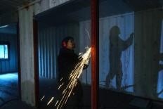Rustono also works in building his new factory. JP/Tarko Sudiarno