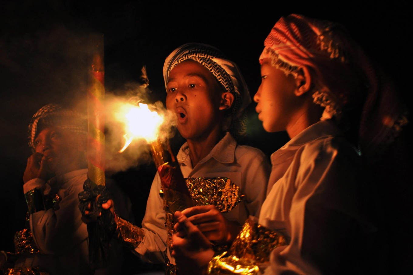 A boy blows out a torch at the close of a takbir torch parade at Makmur Mosque in Basin, Kebonarum, Klaten, Central Java, on Saturday, June 24, 2017. JP/ Magnus Hendratmo