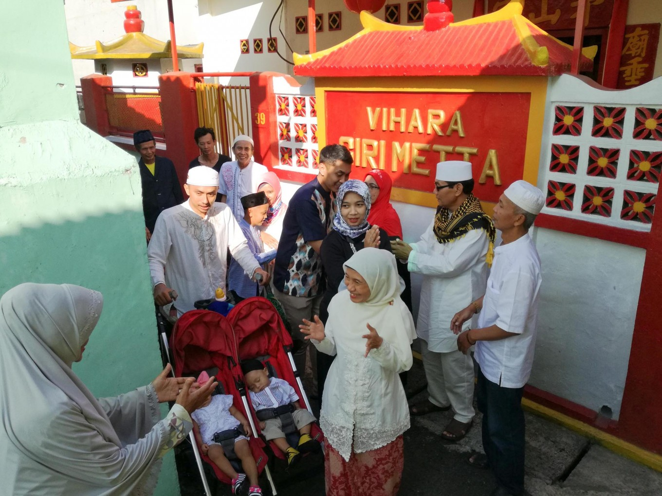 Muslims greet each other in front of a Buddhist temple after observing the Idul Fitri prayer on Gg. Hj Ruhana, Lengkong Kecil, Bandung, on Sunday, June 25, 2017. The people here live among religious diversity, as the 200-meter alley is home to three different houses of worship. JP/Arya Dipa