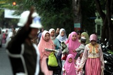 Muslim women walk to Sudirman mosque as an officer guides the way in Denpasar, Bali, to observe the Idul Fitri mass prayer on Sunday, June 25, 2017. JP/ Zul Trio Anggono