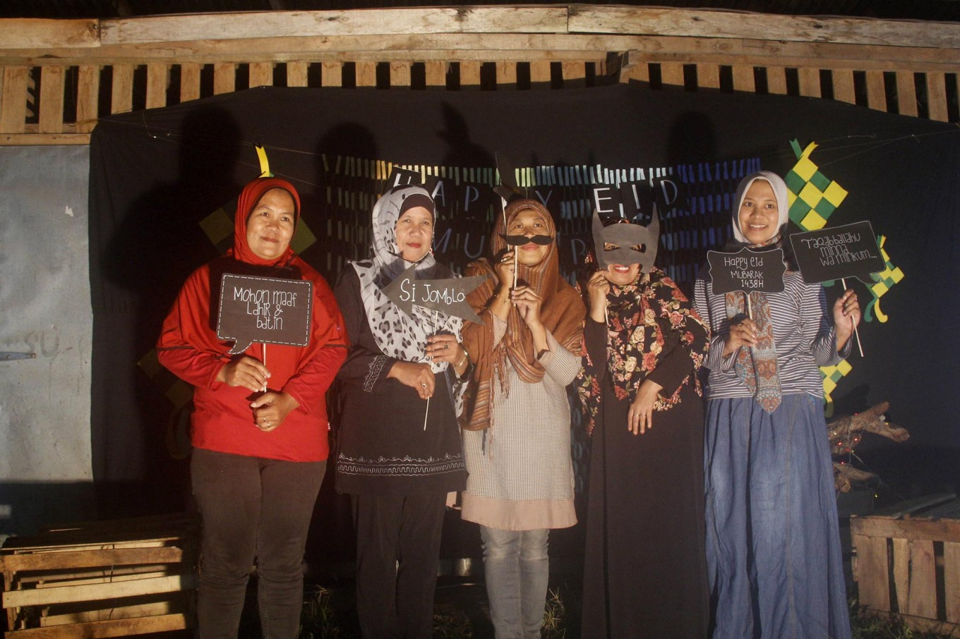 Five women are photographed in a booth built by mosque youths in Payaman Secang, Magelang, Central Java, on Saturday night, June 24, 2017. The eve's festivities included fireworks and a torch parade. JP/Syamsul Huda M.Suhari