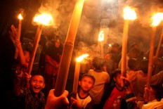 "Children carry bamboo torches aloft during takbiran, chanting ""Allah is great"", on the eve of Idul Fitri at the Kasunanan palace complex in Surakarta, Central Java, on Saturday, June 24, 2017. JP/Ganug Nugroho Adi"
