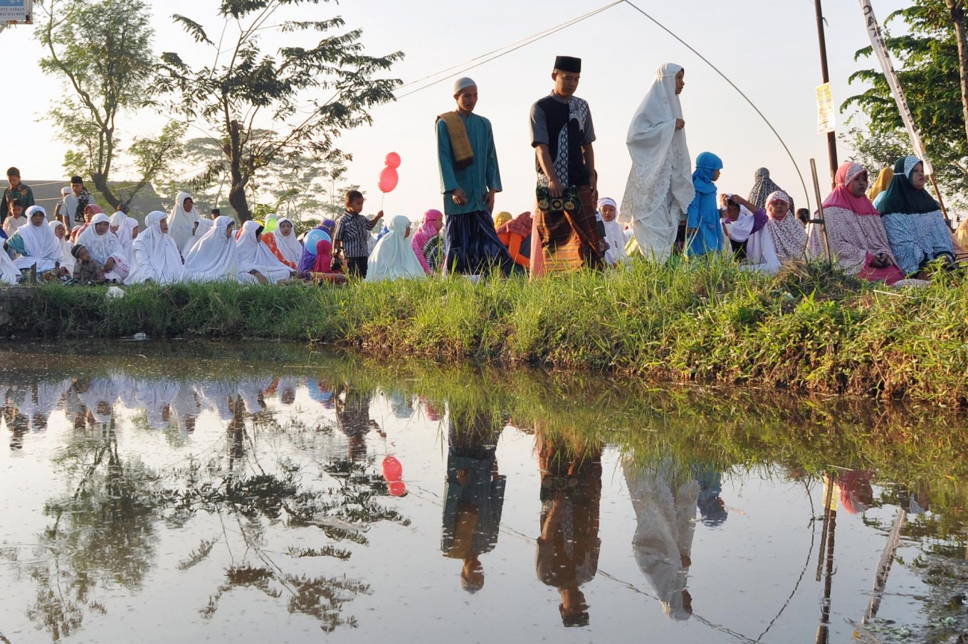 Residents of Nglinggi, Kebonarum, Klaten, Central Java, are reflected in a shallow pool as they prepare for the Ied prayer in a field on Sunday, June 25, 2017. JP/Magnus Hendratmo