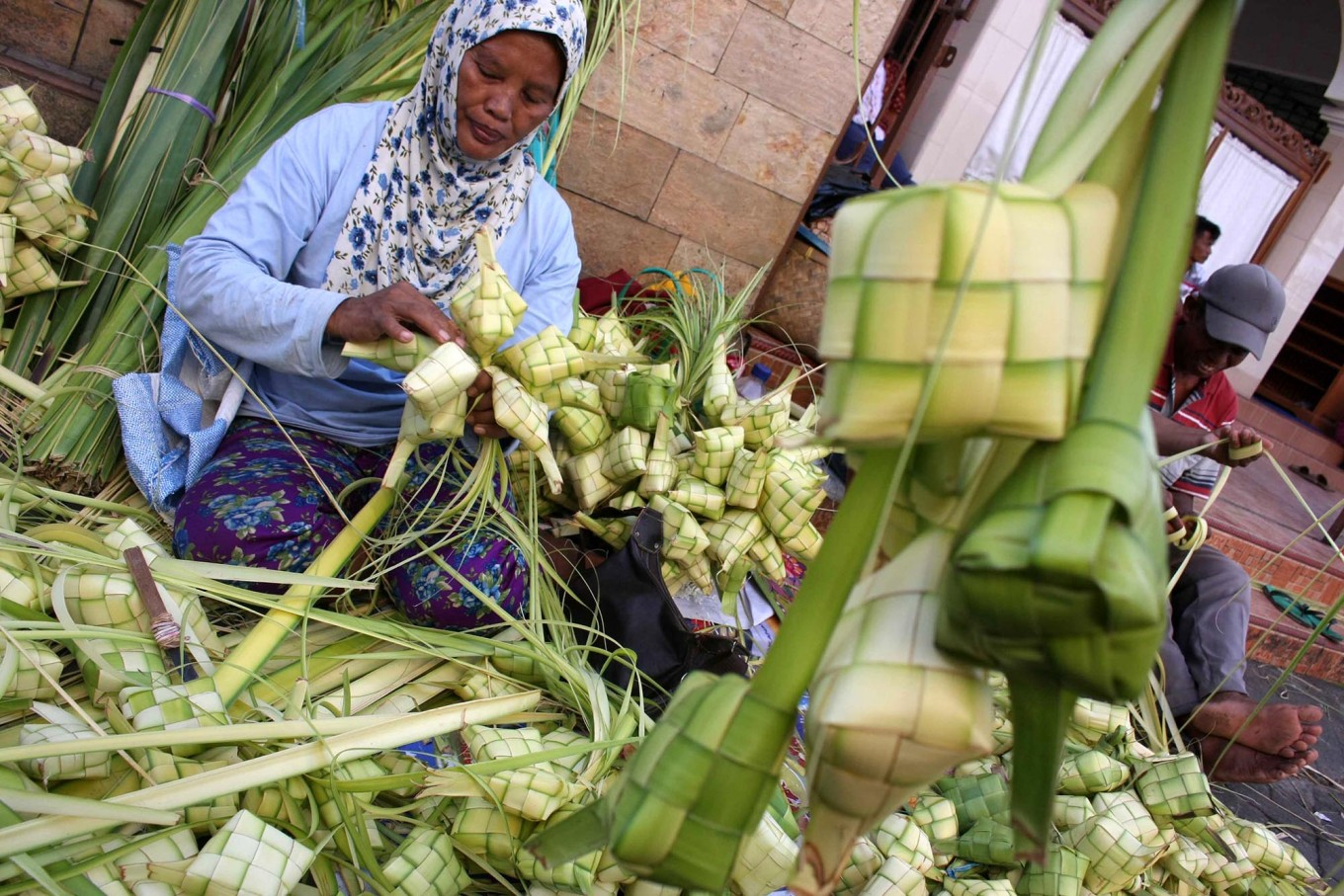 Piece of cake: Warsini, 61, skillfully plaits coconut leaves that will be used to cook ketupat rice cakes in the traditional Legi Market in Surakarta, Central Java. A package containing 10 ready-to-use plaited coconut leaves costs Rp10.000 to Rp15.000 (about US$1). JP/ Ganug Nugroho Adi