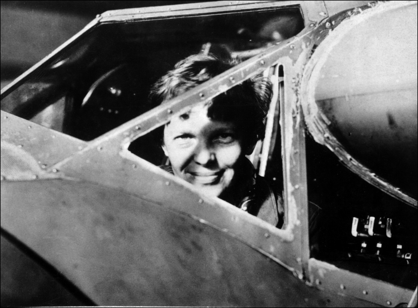 An undated 1930's file photo shows US aviator Amelia Earhart looking through the cockpit window of an aircraft in Essonne,