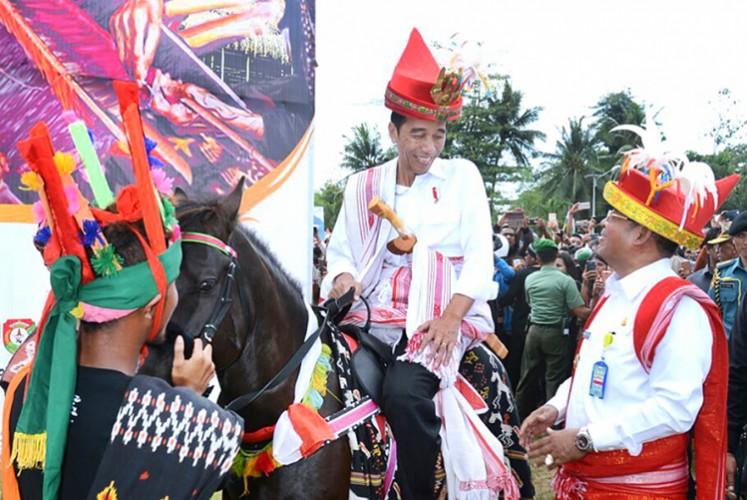 President Joko 'Jokowi' Widodo sits on a sandalwood horse as he talks to Northeast Sumba Regent Markus D. Tallo (right) during the 1001 Sandalwood Parade in Waetabula, Sumba Island, on July 12 2017.