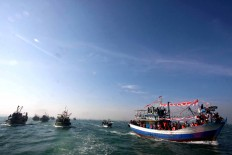 Rows of boats carrying fishermen and visitors are heading to the site where the Lomban Festival takes place in Jepara Bay, Central Java, on July 2. The procession is held by locals to thank God for his blessings and to preserve local culture. JP/Maksum Nur Fauzan
