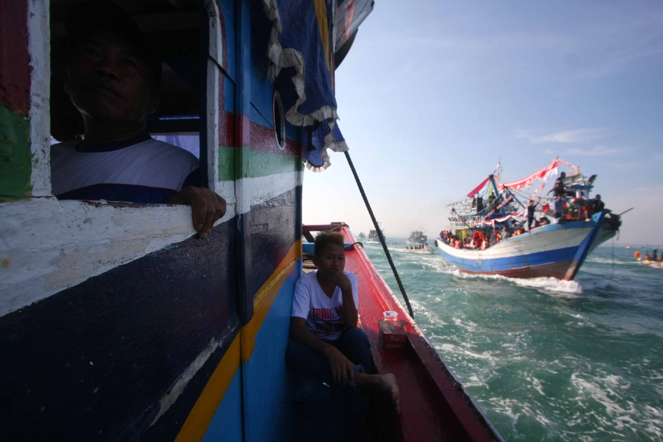 A skipper steers his boat into Jepara Bay in Central Java on July 2 while a young resident sits by the gunwale. JP/Maksum Nur Fauzan