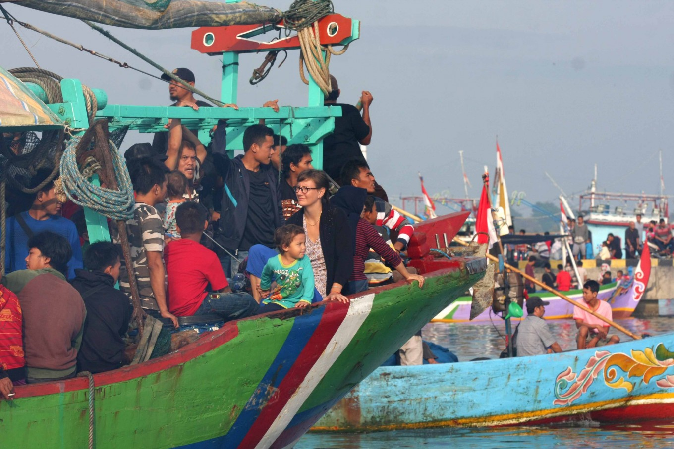 A female tourist sits among locals on board a boat heading for Jepara Bay for the Lomban Festival. JP/Maksum Nur Fauzan