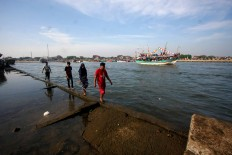 Residents walk along the remains of a damaged wharf with a motor vessel the background during the Lomban Festival on Kartini Beach in Jepara, Central Java, on July 2. JP/Maksum Nur Fauzan