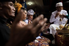 Novi and Kadek sit in front of a priest during a Balinese traditional wedding on Feb. 2. JP/Anggara Mahendra