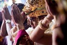 Kadek and Novi perform Hindu prayers during the ceremony at Banjar Taman Yangbatu, Denpasar, on Feb. 2. JP/Anggara Mahendra
