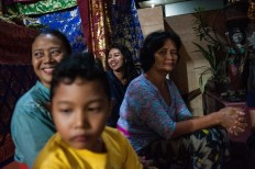 Relatives smile as Novi performs during the Megesah ceremony. JP/Anggara Mahendra