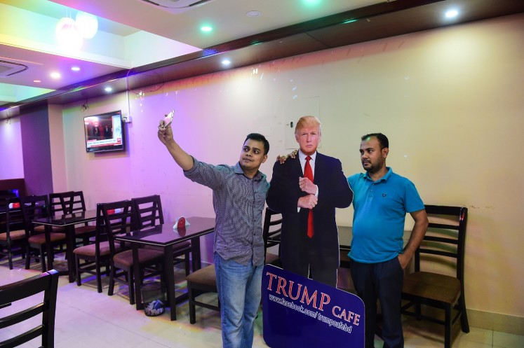 In this photograph taken on July 13, 2017, a Bangladeshi customer takes selfie with a cutout US President Donald Trump at the Trump Cafe in Dhaka.