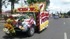 Ready to go: A modified car decorated with flower and vegetable ornaments heads to the festival.  JP/Apriadi Gunawan
