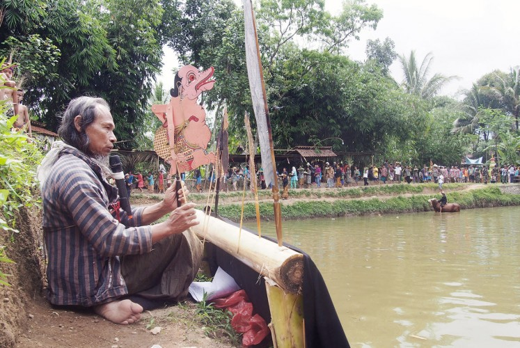 Storyteller: Artist Agus Bimo Prayitno, 58, performs Jantur, a narration using shadow puppets, on the bank of Kedung Bunder.