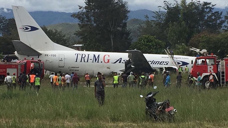 Under investigation: Authorities check the condition of a Tri MG cargo aircraft, which skidded off the runway at Wamena Airport, Papua, on July 18.