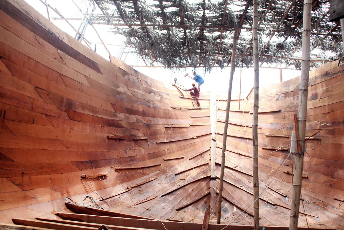 Inside job: The shipbuilders work in precision to ensure the smooth placement of the heavy timbers.