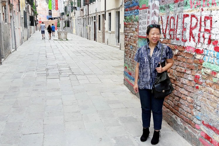 Walk of fame: Artist Tintin Wulia passes an alley in the Arsenale area of Venice, Italy, on her way to the venue of the Art Biennale 2017.