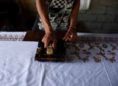 A craftsman stamps the Alas Purwo motif on white fabric at the Batik Satrio cottage industry in Senepo Rejo village, Banyuwangi, East Java, on Saturday, May 20. The workshop produces 13,000 beach sarongs a month. JP/Aman Rochman