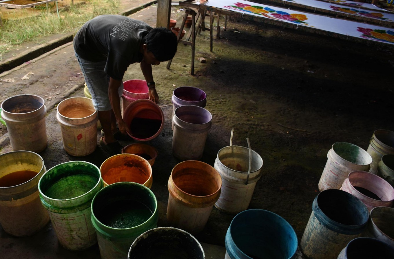 A craftman pours vats of paint in preparation for dyeing beach sarongs. JP/Aman Rochman