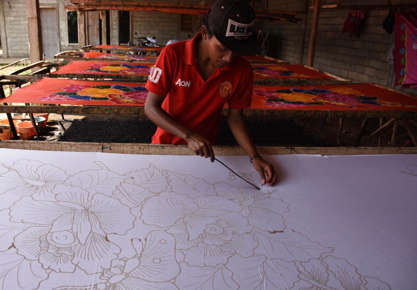 A craftman draws a floral pattern in malam (hot wax) to create a sarong using the wax-resist dyeing technique. JP/Aman Rochman